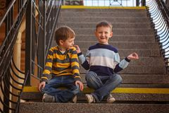 Peu deux garçons s'asseyant sur l'escalier dans le jour ensoleillé Images libres de droits