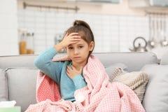 Peu douleur de fille de toux et mal de tête sur le sofa images libres de droits