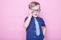 Peu enfant adorable en lien et verres école précours Mode Portrait de studio au-dessus de fond rose image libre de droits