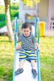 Peu enfant asiatique jouant la glissière au terrain de jeu Photos libres de droits