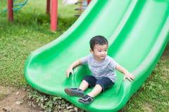 Peu enfant asiatique jouant la glissière au terrain de jeu Photo libre de droits