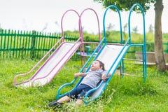 Peu enfant asiatique jouant la glissière au terrain de jeu Images libres de droits