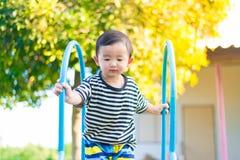 Peu enfant asiatique jouant la glissière au terrain de jeu Photographie stock libre de droits