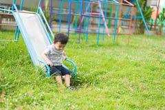 Peu enfant asiatique jouant la glissière au terrain de jeu Photos stock