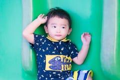 Peu enfant asiatique jouant la glissière au terrain de jeu Photographie stock