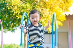 Peu enfant asiatique jouant la glissière au terrain de jeu Image libre de droits