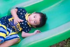 Peu enfant asiatique jouant la glissière au terrain de jeu Images stock