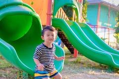 Peu enfant asiatique jouant la glissière au terrain de jeu Image stock