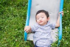 Peu enfant asiatique jouant la glissière au terrain de jeu, accident Image stock