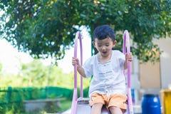 Peu enfant asiatique jouant la glissière au terrain de jeu sous le sunli Photos stock