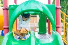 Peu enfant asiatique jouant la glissière au terrain de jeu sous le sunli Image stock