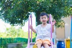 Peu enfant asiatique jouant la glissière au terrain de jeu sous le sunli Image libre de droits