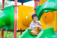 Peu enfant asiatique jouant la glissière au terrain de jeu sous le sunli Photo libre de droits
