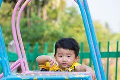 Peu enfant asiatique jouant la glissière au terrain de jeu sous le sunli Photos libres de droits