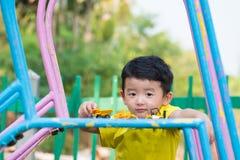 Peu enfant asiatique jouant la glissière au terrain de jeu sous le sunli Images stock