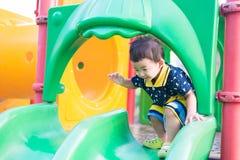 Peu enfant asiatique jouant la glissière au terrain de jeu sous le sunli Photographie stock