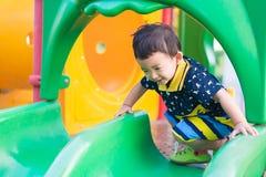Peu enfant asiatique jouant la glissière au terrain de jeu sous le sunli Images libres de droits