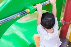 Peu enfant asiatique jouant la glissière au terrain de jeu sous le sunli Photo stock