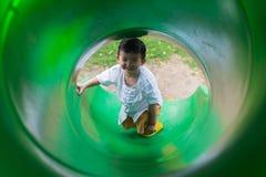 Peu enfant asiatique montant la glissière au terrain de jeu dans le résumé Photo libre de droits