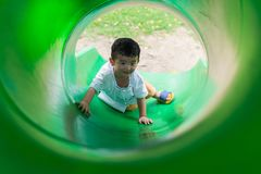 Peu enfant asiatique montant la glissière au terrain de jeu dans le résumé Image libre de droits