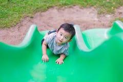 Peu enfant asiatique montant la glissière au terrain de jeu dans le résumé Photographie stock