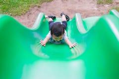 Peu enfant asiatique montant la glissière au terrain de jeu dans le résumé Images libres de droits