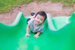 Peu enfant asiatique montant la glissière au terrain de jeu dans le résumé Images stock