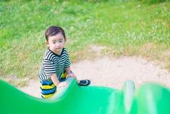 Peu enfant asiatique montant la glissière au terrain de jeu dans le résumé Photo stock