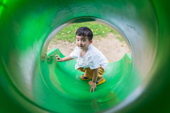 Peu enfant asiatique montant la glissière au terrain de jeu dans le résumé Photographie stock libre de droits