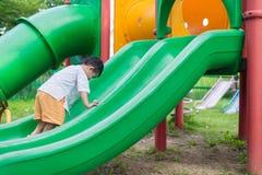 Peu enfant asiatique montant la glissière au terrain de jeu dans le résumé Image stock