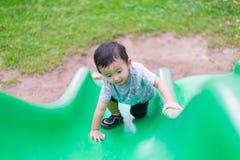 Peu enfant asiatique montant la glissière au terrain de jeu en été, DOF peu profond Images libres de droits