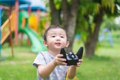 Peu enfant asiatique tenant un à télécommande et un x28 par radio ; Han de contrôle photographie stock