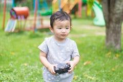 Peu enfant asiatique tenant un à télécommande et un x28 par radio ; Han de contrôle photos libres de droits