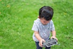 Peu enfant asiatique tenant un à télécommande et un x28 par radio ; Han de contrôle image libre de droits