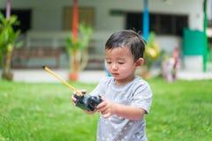 Peu enfant asiatique tenant un à télécommande et un x28 par radio ; Han de contrôle photographie stock libre de droits