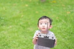Peu enfant asiatique tenant un à télécommande et un x28 par radio ; Han de contrôle images stock