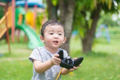 Peu enfant asiatique tenant un à télécommande et un x28 par radio ; Han de contrôle photo stock