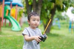 Peu enfant asiatique tenant un à télécommande et un x28 par radio ; Han de contrôle photo libre de droits