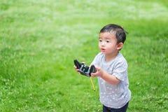 Peu enfant asiatique tenant un à télécommande et un x28 par radio ; Han de contrôle Images libres de droits