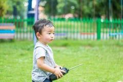 Peu enfant asiatique tenant un à télécommande et un x28 par radio ; Han de contrôle Image stock