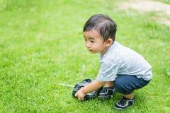 Peu enfant asiatique tenant un Han de contrôle à télécommande par radio Image stock