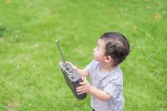 Peu enfant asiatique tenant un Han de contrôle à télécommande par radio Photo libre de droits