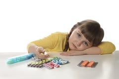 Peu enfant avec beaucoup de différentes pilules sur le blanc Danger d'intoxication de m?dicament photos stock