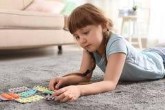 Peu enfant avec beaucoup de différentes pilules sur le plancher Danger d'intoxication de m?dicament images stock