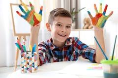 Peu enfant avec les mains peintes à la table photo libre de droits