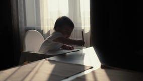 Peu enfant mignon de fille frappe le crayon sur la table et les répétitions après maman banque de vidéos
