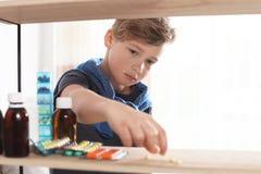 Peu enfant prenant des pilules d'étagère Danger d'intoxication de m?dicament photographie stock