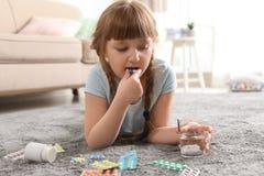 Peu enfant prenant la pilule sur le plancher Danger d'intoxication de m?dicament photos stock