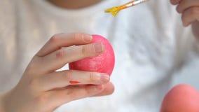 Peu enfant utilisant la brosse avec la peinture jaune pour décorer l'oeuf de pâques teint, créativité banque de vidéos