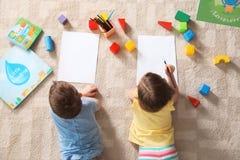 Peu enfants dessinant à l'intérieur ?tude et jouer images libres de droits